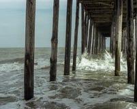 Ondas que se estrellan contra los posts de madera del embarcadero Imagen de archivo