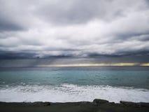 Ondas que se estrellan en la playa con las nubes de tormenta fotografía de archivo