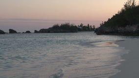 Ondas que se estrellan en la playa de Bermudas en la puesta del sol almacen de video