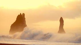 Ondas que se estrellan en la roca en la playa negra en Islandia almacen de metraje de vídeo