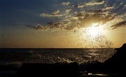 Ondas que se estrellan en las rocas durante puesta del sol Imagen de archivo