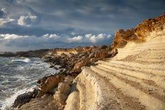 Ondas que se estrellan en las rocas, el sol y las nubes fuertes antes del ra Imagenes de archivo