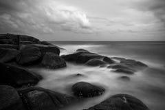 Ondas que se estrellan en rocas fotografía de archivo