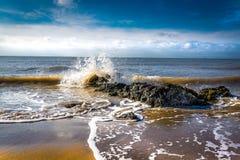 Ondas que se estrellan en rocas en la costa Imagen de archivo