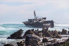 Ondas que se estrellan por un viejo naufragio aherrumbrado Hogar a los cormoranes, a las gaviotas y a otros pájaros fotografía de archivo
