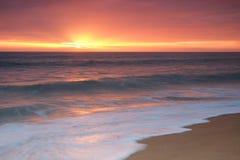 Ondas que se estrellan sobre la orilla durante tarde Fotos de archivo