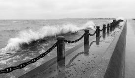 Ondas que se estrellan sobre pilares y cadena del embarcadero en la línea de la playa Foto de archivo