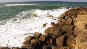 Ondas que se rompen contra rocas en línea de la playa del mar almacen de video