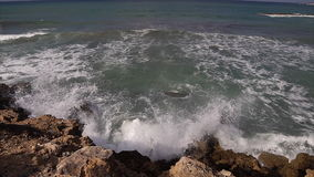 Ondas que se rompen contra rocas en línea de la playa del mar metrajes