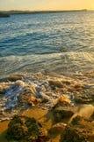 Ondas que se rompen en la playa de la arena en la puesta del sol Imagenes de archivo