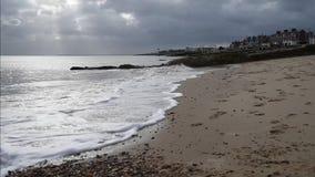 Ondas que se rompen en la playa de Felixstowe con los rayos del sol almacen de video