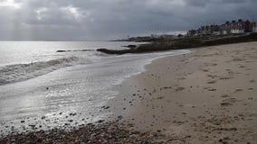 Ondas que se rompen en la playa de Felixstowe con los rayos del sol que aparecen almacen de metraje de vídeo