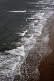 Ondas que se rompen en una playa arenosa Imagen de archivo