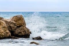 Ondas que se rompen en una roca Imagenes de archivo