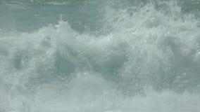 Ondas que se rompen implacablemente en la orilla almacen de video