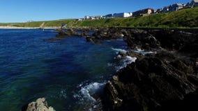 Ondas que traslapan en roca en primero plano con la vista de la bahía y de la playa distante, Cornualles de Fistral almacen de metraje de vídeo