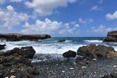 Ondas que traslapan la orilla de la playa de piedra negra en Aruba Fotografía de archivo