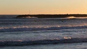 Ondas que vienen a la playa en un día ventoso metrajes