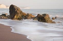 Ondas Receding sobre o litoral rochoso Fotos de Stock