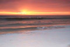 Ondas sobre la orilla durante puesta del sol Foto de archivo