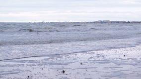 Ondas tempestuosas con espuma en el mar Playa de la arena en invierno almacen de metraje de vídeo