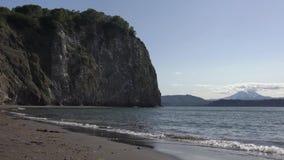Ondas tranquilas en el mar, playa de la arena volcánica negra, orillas rocosas del Océano Pacífico almacen de metraje de vídeo