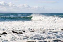 Ondas y personas que practica surf de gran alcance Fotografía de archivo