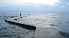 Ondas y pescador en el lago almacen de metraje de vídeo