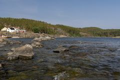 Ondas y rocas en costa en primero plano y montaña con delantera fotos de archivo
