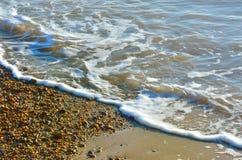 Ondas y tabla en línea de la playa Fotografía de archivo
