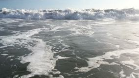 Onde blu che praticano il surfing sulla spiaggia tropicale dell'oceano stock footage