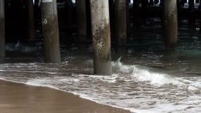 Onde che colpiscono gli accatastamenti per Pier Santa Monica Sand Beach stock footage