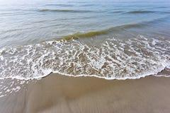 Onde che raggiungono spiaggia sabbiosa fotografia stock libera da diritti