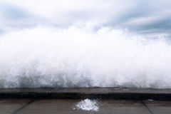 Onde che si rompono sulla riva di pietra Fotografie Stock Libere da Diritti