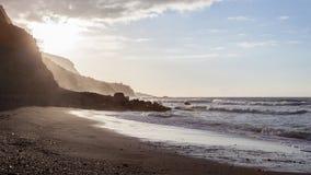 Onde che si rompono sulla riva di una spiaggia di Tenerife con luce posteriore del tramonto imminente immagine stock