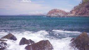 Onde che si schiantano al rallentatore sulle rocce sul litorale stock footage