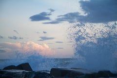 Onde che si schiantano sul frangiflutti davanti ad un cielo blu w di tramonto Immagine Stock Libera da Diritti