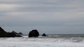 Onde che si schiantano sulle rocce della riva con il cielo nuvoloso archivi video
