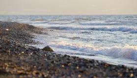 Onde che spruzzano ad una spiaggia immagini stock