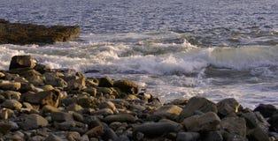 Onde che spruzzano dentro sulle rocce su una sera calda di estate Fotografia Stock