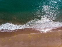 Onde che spruzzano la vista aerea della riva di mare immagine stock libera da diritti