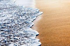 Onde che spruzzano sulla spiaggia sabbiosa Fotografia Stock Libera da Diritti
