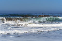 Onde che spruzzano sulle rocce enormi, fuori dalla riva, Fotografie Stock Libere da Diritti
