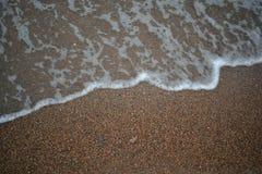 Onde con schiuma contro lo sfondo della sabbia Immagini Stock