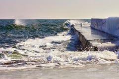 Onde con schiuma contro waterbreaker Fotografie Stock Libere da Diritti