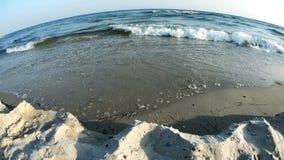 Onde del mare che rotolano su una spiaggia sabbiosa stock footage