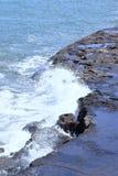 Onde del mare che spruzzano contro le rocce fotografie stock libere da diritti