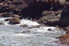 Onde del mare che spruzzano contro le rocce e che entrano in caverna della roccia fotografia stock libera da diritti