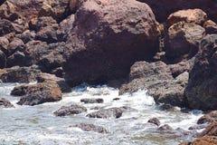 Onde del mare che spruzzano contro le rocce e che entrano in caverna della roccia immagini stock libere da diritti