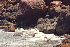 Onde del mare che spruzzano contro le rocce e che entrano in caverna della roccia immagine stock libera da diritti